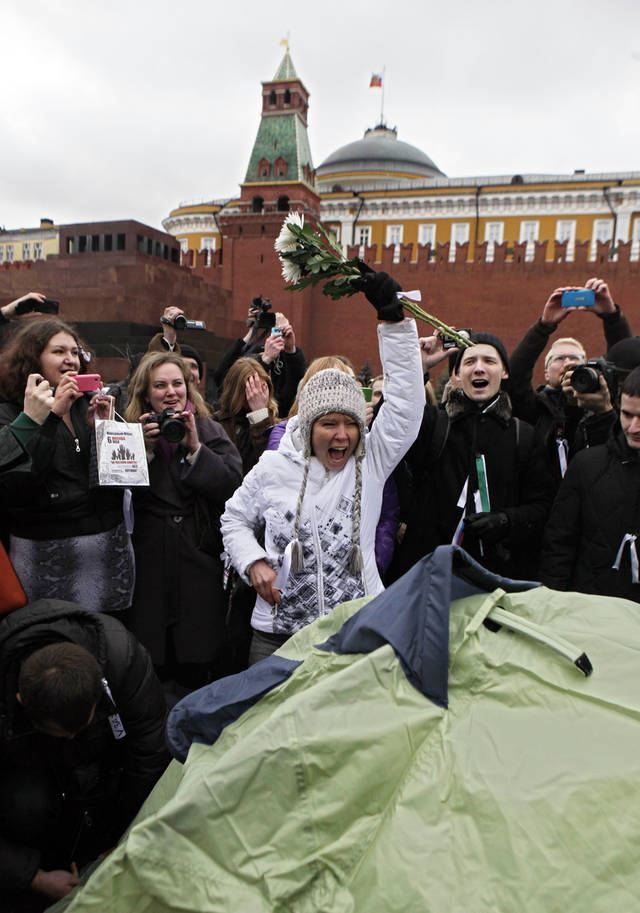 Opposition leader Yevgeniya Chirikova, center, gestures after putting up a tent during a protest at the Red Square in Moscow, Sunday, April 8, 2012. Police arrested prominent opposition leader along with several other activists when they tried to put up a small tent on the Red Square. Opposition activists called for supporters to walk around Red Square on Sunday wearing the white ribbons that have become a symbol of the protest movement against Prime Minister Vladimir Putin. Putin will begin serving a third presidential term in May. (AP Photo/Maria Turchenkova)
