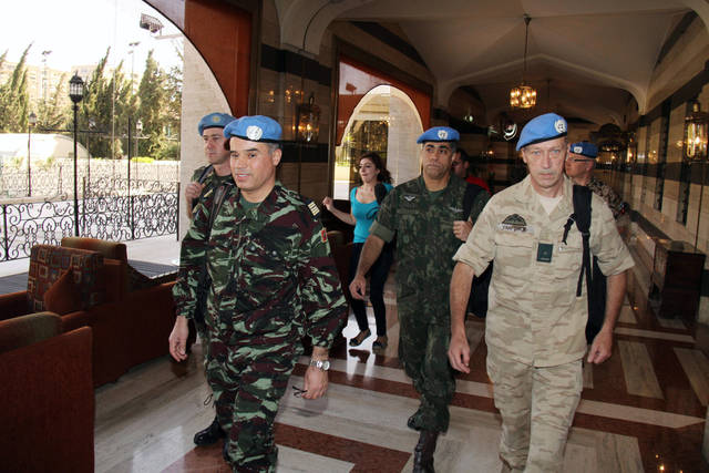 U.N. observers, led by Moroccan Col. Ahmed Himmiche, left, leave the Sheraton Hotel in Damascus, Syria, Monday, April 16, 2012. An advance team of U.N. observers on Monday was working out with Syrian officials the ground rules for monitoring the country's 5-day old cease-fire, which appeared to be rapidly unraveling as regime forces pounded the opposition stronghold of Homs with artillery shells and mortars, activists said. (AP Photo/Bassem Tellawi)