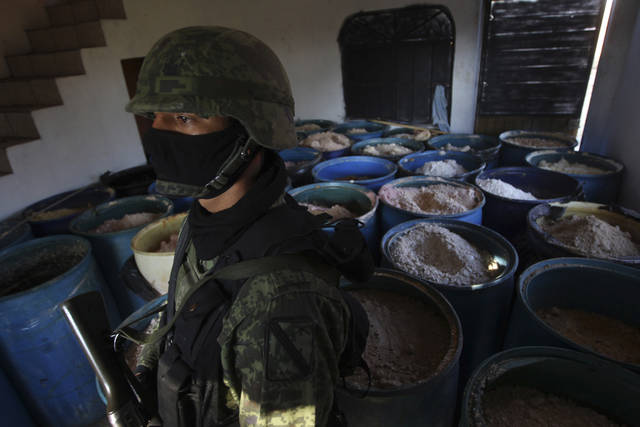 "FILE - In this Feb. 9, 2012, file photo a soldier stands in a room full of barrels containing white and yellow powder after a seizure of 15 tons of pure methamphetamine at a small ranch in Tlajomulco de Zuniga, on the outskirts of Guadalajara, Mexico. Mexican drug cartels are flooding U.S. cities with cheap, extraordinarily pure methamphetamine made in factory-like ""super labs� _ a surge in production that has all but negated the nation's long effort to curb meth production at home with tighter controls on key ingredients. (AP Photo/Bruno Gonzalez, File)"