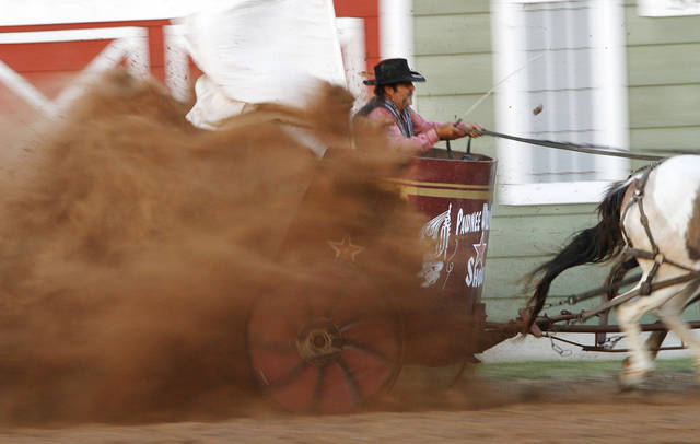 Kevin Webb rides through a cloud of dust in a horse pulled chariot during the chariot races at the Pawnee Bill Wild West Show in Pawnee, Oklahoma on Saturday,  June 23, 2012.  Photo by Jim Beckel, The Oklahoman