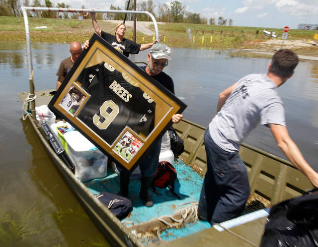   Russell Wilson unloads a water damaged Drew Brees signed shirt for his daughter Amy Keller and her husband Michael from their Braithwaite, La. home, Saturday September 1, 2012. It was the first time the Keller family was able to get tho their flooded home since Hurricane Isaac storm surge inundated the area. (AP Photo/The Times-Picayune, David Grunfeld) MAGS OUT; NO SALES; USA TODAY OUT  
