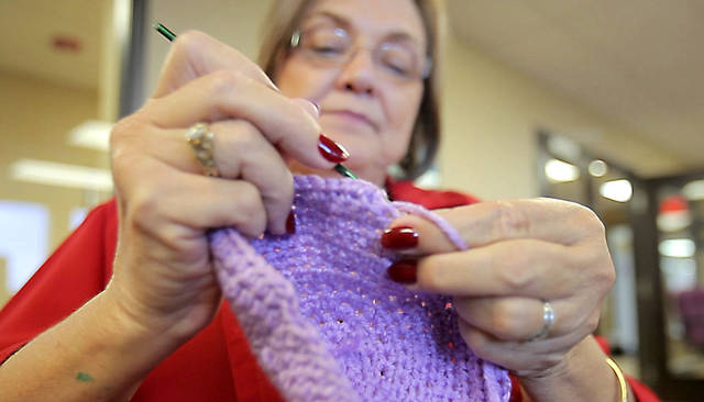 Above: Penny Hill-Malone crochets a purple cap for the �Click for Babies, Period of Purple Crying Caps.�  At right: A box of caps made for the program, which raises awareness about normal infant crying and the dangers of shaking a baby.  Photos by David McDaniel,  The Oklahoman