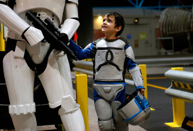 Michael Elden, 5, of Blanchard, looks up at his father Mark Elden as they get their picture taken during the Science Museum Oklahoma for the Bright Night of Star Wars sleepover on Friday, March 15, 2013. Photo by Bryan Terry, The Oklahoman