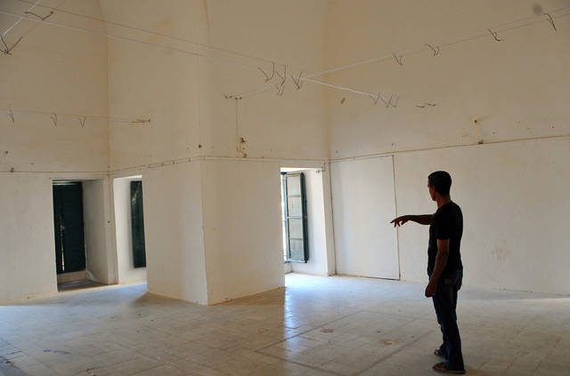 In this Thursday, July 26, 2012 photo a man points at the empty art gallery in La Marsa, Tunis. The Spring of the Arts exhibit in the wealthy Tunis suburb of La Marsa triggered June riots that left one dead and 100 injured. Many of the paintings questioned religion's role in society, including some clearly skewering Salafis .(AP Photo/Hassene Dridi)