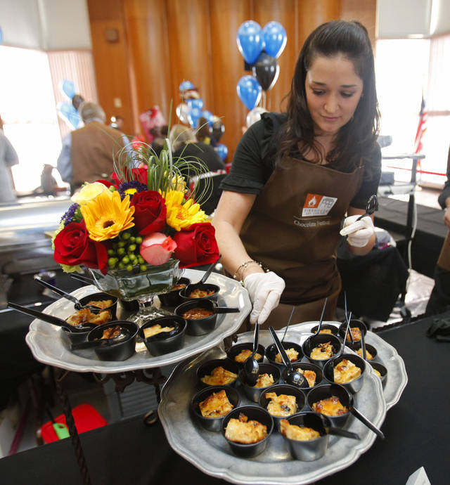 Taylor Cain, with Interurban Restaurant, sets out chocolate samples Saturday at the 29th annual Chocolate Festival sponsored by Firehouse Art Center. PHOTO BY STEVE SISNEY, THE OKLAHOMAN