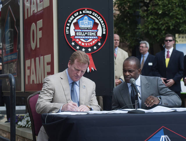 NFL Comissioner Roger Goodell, signs as NFLPA Executive Director DeMaurice Smith watches at the signing of their collective bargaining agreement at the Pro Football Hall of Fame in Canton, Ohio, Friday, Aug. 5, 2011. (AP Photo/Phil Long)