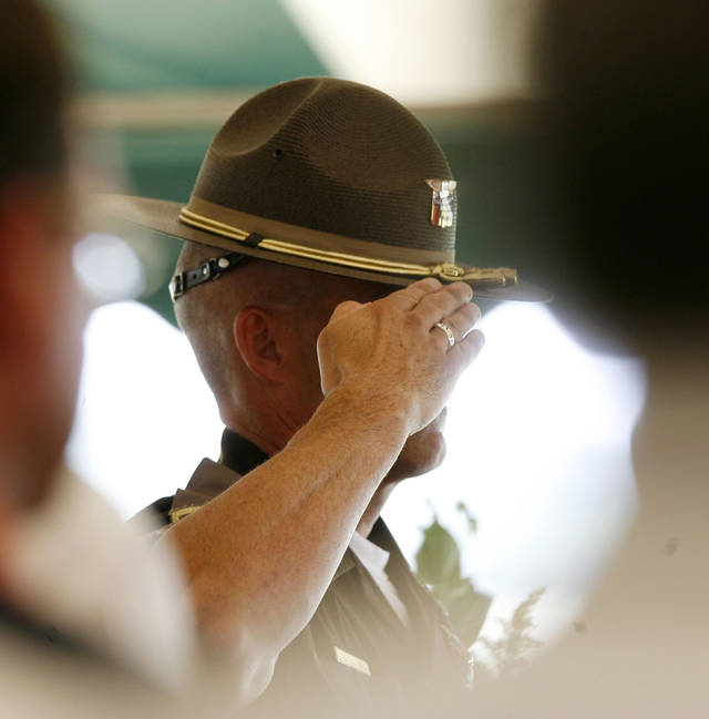 An Oklahoma Highway Patrol Trooper salutes during the memorial service for former congressman and rodeo announcer Clem McSpadden in Chelsea, OK, Saturday, July 12, 2008. BY PAUL HELLSTERN, THE OKLAHOMAN