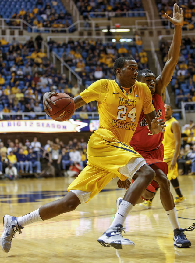 West Virginia's Aaric Murray (24) drives by Radford's Jalen Carethers, right, during the second half of an NCAA college basketball game at WVU Coliseum in Morgantown, W.Va., Saturday, Dec. 22, 2012. West Virginia defeated Radford 72-62. (AP Photo/David Smith)