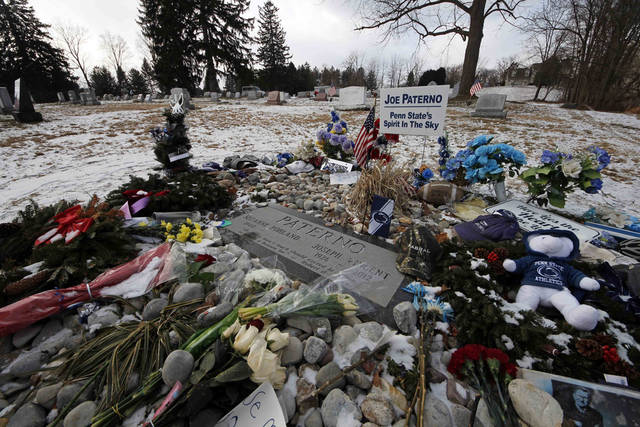 Momentos surround the headstone at the grave of former Penn State head football coach Joe Paterno, Tuesday, Jan. 22, 2013, in State College, Pa. Supporters of Paterno are marking the 1-year anniversary of his death with a candlelight vigil Tuesday night. (AP Photo/Gene J. Puskar)