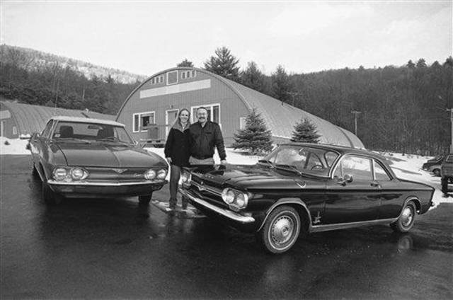 Cal and Joan Clark stand between a pair of Chevrolet Corvairs outside their Shelburne, Mass., mail-order parts company which for 12 years has catered to the car that went out of production in the 1960s, Jan. 31, 1985. (AP Photo/Nick Noyes)