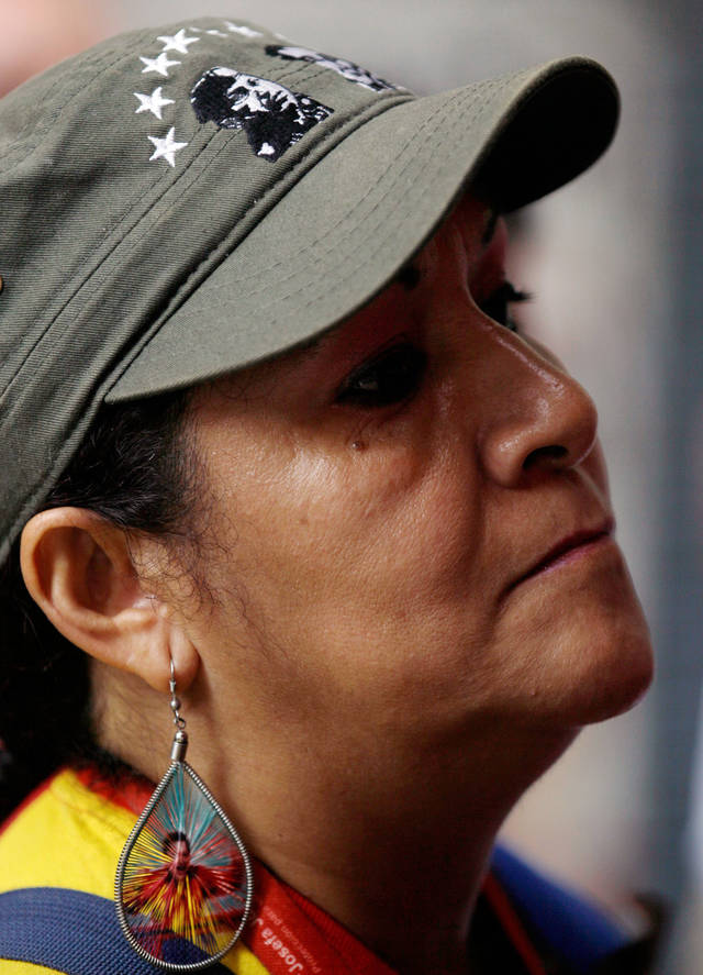 A woman donning images of  Venezuela's President Hugo Chavez attends an outdoor church service in front of the National Assembly, where supporters of  gathered to pray for his health, in Caracas,Venezuela, Thursday, Dec. 13, 2012.  Venezuelans were warned that their ailing president may not be well enough after his fourth cancer-related surgery in Cuba to be inaugurated on Jan. 10.  (AP Photo/Fernando Llano)