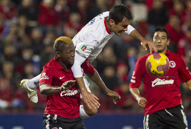 Tijuana's Duvier Riascos, left, fights for the ball with Toluca's Edgar Duenas during a Mexican soccer league match in Tijuana, Mexico, Thursday, Nov. 29, 2012. (AP Photo/Christian Palma)