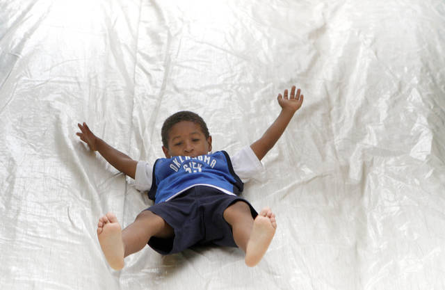 Julius Ejike-Charles, 5, of Oklahoma City slides down a slide before game five of the Western Conference semifinals between the Memphis Grizzlies and the Oklahoma City Thunder in the NBA basketball playoffs at Oklahoma City Arena in Oklahoma City, Wednesday, May 11, 2011. Photo by Sarah Phipps, The Oklahoman