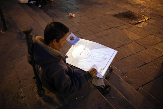Artist Jose Garcia works on a drawing of Pope Benedict XVI as he sits in the main square in Leon, Mexico, Thursday March 22, 2012. Pope Benedict XVI will arrive in Mexico Friday, a decade after his predecessor's last visit, to a very different country and a church that has suffered debilitating setbacks amidst sex abuse scandals and a lower percentage of Mexicans who call themselves Catholic today, compared to a decade ago. (AP Photo/Alexandre Meneghini)