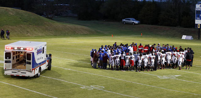Players, coaches and officials stand in a circle around Millwood's Andre Clanton (22) as emergency medical workers check on Clanton during a high school football game between Millwood and Prime Prep Academy in Oklahoma City, Friday, Sept. 14, 2012. Clanton was taken from the game in an ambulance. Photo by Nate Billings, The Oklahoman