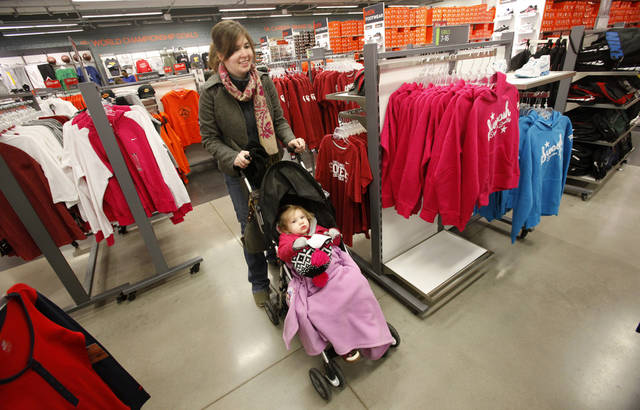 Christa Curtis, Okla. City, navigates racks of clothing with her daughter Emmelyne, 2, in the Nike store at The Outlet Shoppes of Oklahoma City in Oklahoma City Friday, Dec, 23, 2011. Photo by Paul B. Southerland, The Oklahoman