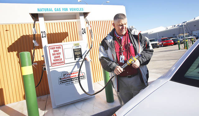 Patrick Morris with Oklahoma City's fleet services division prepares to fill a vehicle with compressed natural gas in December.  Photo by Paul Southerland,  The Oklahoman