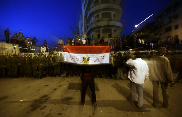 A protester holds the Egyptian national flag as army soldiers stand guard near the presidential palace in Cairo, Egypt, Sunday, Dec. 9, 2012. Egypt's liberal opposition called for more protests Sunday, seeking to keep up the momentum of its street campaign after the president made a partial concession overnight but refused its main demand he rescind a draft constitution going to a referendum on Dec. 15. (AP Photo/Hassan Ammar)