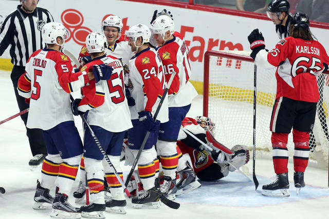 Florida Panthers' Aaron Ekbald (5), Brian Campbell (51) Brad Boyes (24) Jonathan Huberdeau (11) celebrate a goal by Aleksander Barkov (16) as Ottawa Senators' Erik Karlsson (65) looks on during first period NHL hockey action in Ottawa, Ontario, on Saturday, Feb, 21, 2015. (AP Photo/The Canadian Press, Fred Chartrand)
