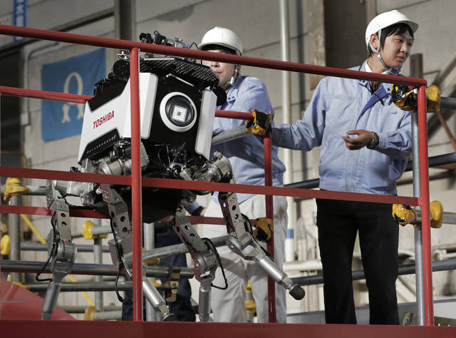 Toshiba Corp.'s nuclear inspection robot breaks down as its staff look on during a demonstration at a Toshiba factory in Yokohama, west of Tokyo, Wednesday, Nov. 21, 2012. The four-legged robot is designed to help at the meltdown-crippled Japanese nuclear plant, climbing over debris and venturing into radiated areas off-limits to human workers. The robot took a jerky misstep during a demonstration to reporters, freezing with one leg up in the air. It had to be lifted by several people and rebooted. (AP Photo/Itsuo Inouye)