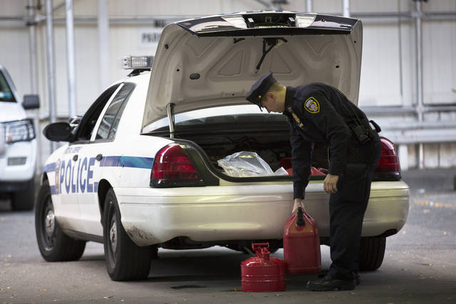A Federal Reserve officer stocks his vehicle's trunk with filled fuel containers at the 10th Avenue Hess station, Saturday, Nov. 3, 2012, in New York. Damage wreaked by Superstorm Sandy prevented fuel shipments throughout the metropolitan area for days, leading to shortages and long queues that continue into the weekend. (AP Photo/ John Minchillo) ORG XMIT: NYJM106