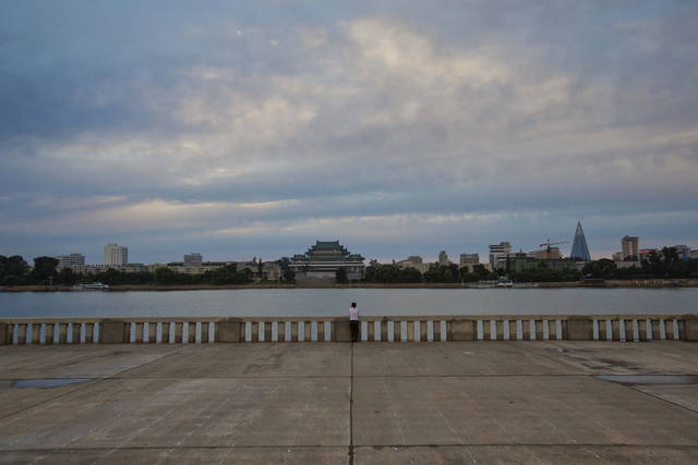 In this Thursday, Sept. 13, 2012 photo, a woman stands along the bank of the Taedong River at the end of the day in Pyongyang, North Korea. (AP Photo/David Guttenfelder)