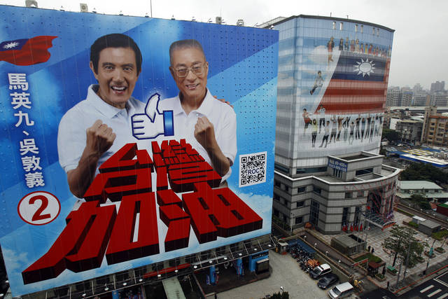 "A massive campaign poster hangs next to the ruling KMT, Nationalist Party, headquarters showing incumbent President Ma Ying-jeou, left, and his running mate Premier Wu Den-yih under the translation that reads ""Taiwan Go! Go!"" in Taipei, Taiwan, Thursday, Dec. 15, 2011. Taiwan's presidential candidates began their final month of campaigning Thursday, in a race that is being closely watched in Beijing and Washington. The presidential election is to be held on January 14, 2012. (AP Photo/Wally Santana)"