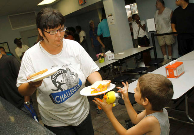 Miranda Bryant, of Tulsa, hands a meal to her son, Ian, 6, on Friday at the Iron Gate in Tulsa. Photo by James Gibbard, Tulsa World