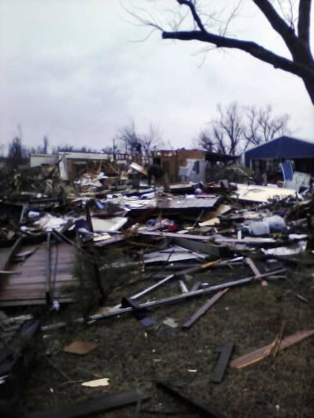 In this photo taken with a cell phone, damage to a barn and a house is shown in Cincinnati, Ark., Friday, Dec. 31, 2010. A Washington County Sheriff's Office dispatcher says three people have died after a tornado slammed into the tiny northwest Arkansas town of Cincinnati. (AP Photo/Siloam Springs Herald Leader via The Benton County Daily Record, Melissa Gute)