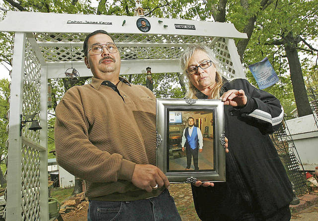 Duane and Donna Kerns on May 2 hold the last photograph taken of their son, Colton — a picture of him in his prom clothes the day before he died in a crash after drinking and driving.  Photo by James Gibbard, Tulsa World