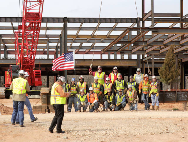 Iron workers pose around the topping-out beam, as Mercy Edmond holds their topping out ceremony and blessing of the new facility in Edmond, OK, Monday, Feb. 27, 2012. By Paul Hellstern, The Oklahoman