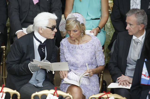 German fashion designer Karl Lagerfeld, left, takes his seat at the Monaco palace for the religious wedding ceremony of Prince Albert II of Monaco and Charlene Princess of Monaco, Saturday, July 2, 2011.. (AP Photo/Lionel Cironneau, Pool)