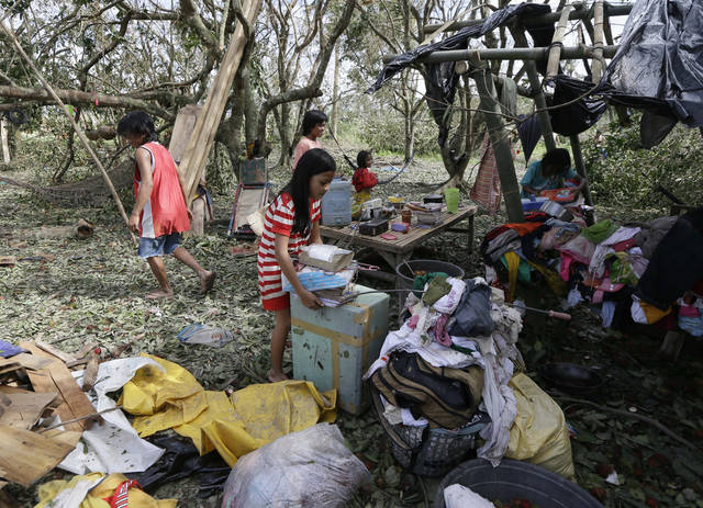 Children retrieve their books and other belongings from their damaged home Wednesday Dec. 5, 2012, a day after powerful Typhoon Bopha hit Montevista township, in the Compostela Valley in southern Philippines. Typhoon Bopha (local name Pablo), one of the strongest typhoons to hit the Philippines this year, barreled across the country's south on Tuesday, killing scores of people and forcing more than 50,000 to flee from inundated villages. (AP Photo/Bullit Marquez)