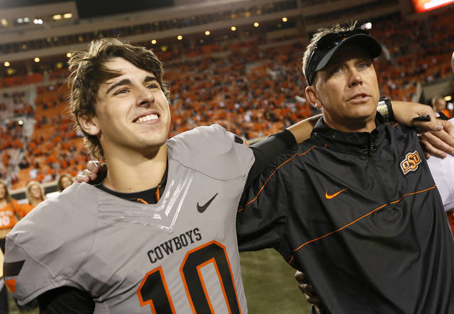 Oklahoma State's Clint Chelf (10) smiles as he sings the alma mater with offensive coordinator Todd Monken and  the rest of the team after a college football game between Oklahoma State University (OSU) and West Virginia University (WVU) at Boone Pickens Stadium in Stillwater, Okla., Saturday, Nov. 10, 2012. OSU won, 55-34. Photo by Nate Billings, The Oklahoman