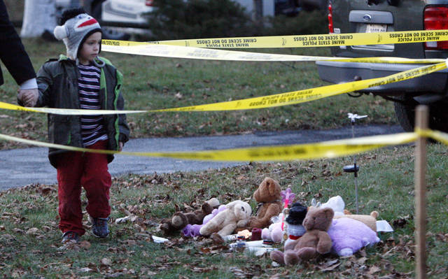 Isaiah Vear, 5, of Waterville, Maine, leaves a memorial after placing a toy for missing 20-month-old Ayla Reynolds outside the toddler's home, Thursday, Dec. 22, 2011, in Waterville. investigators put up crime scene tape around the house on Thursday. (AP Photo/Robert F. Bukaty)