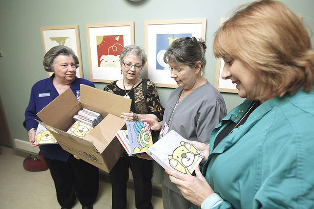 "Martha Aughe, left, and Lin Copelin, second from left, deliver children's books Wednesday to neonatal intensive care nurses Kathy Milam, second from right, and Vickie Cotton at the Norman Regional Healthplex Women's and Children's Center. Hospital staff will give a copy ot ""That's Not My Teddy"" to parents of newborns. PHOTO BY STEVE SISNEY, THE OKLAHOMAN"
