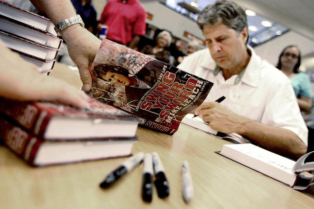 "Former Texas Tech football coach Mike Leach signs copies of his new book, ""Swing Your Sword,"" at a Barnes & Noble on Tuesday, July 19, 2011, in Lubbock, Texas. (AP Photo/The Avalanche-Journal, Miranda Grubbs) ORG XMIT: TXLUB105"