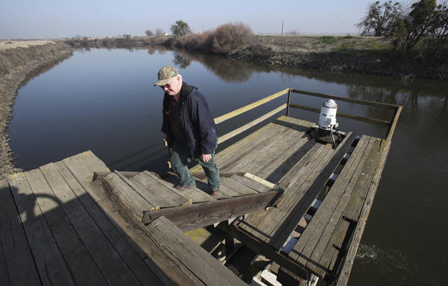 FILE - In this Jan. 16, 2009 file photo, farmer Mike Robinson is seen after inspecting a pump used to draw water from the San Joaquin River to irrigate his family farm in the Sacramento-San Joaquin Delta near Stockton, Calif. California and federal officials are set to make an announcement Wednesday, July 25, 2012 about multi-billion dollar plans to build a massive twin tunnel system to carry water from the Sacramento-San Joaquin River Delta to farmland and cities. (AP Photo/Rich Pedroncelli, File)
