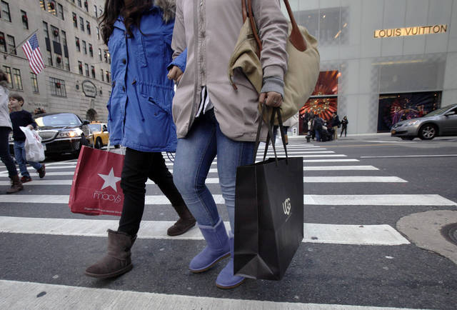 Shoppers on New York's Fifth Ave. carry bags with their purchases, Friday, Nov. 23, 2012. Black Friday, the day when retailers traditionally turn a profit for the year, got a jump start this year as many stores opened just as families were finishing up Thanksgiving dinner. (AP Photo/Richard Drew)