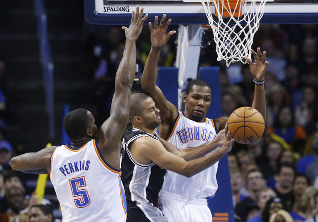 San Antonio Spurs guard Tony Parker (9) passes off between Oklahoma City Thunder center Kendrick Perkins (5) and forward Kevin Durant (35) in the second quarter of an NBA basketball game in Oklahoma City, Wednesday, Nov. 27, 2013. (AP Photo/Sue Ogrocki)