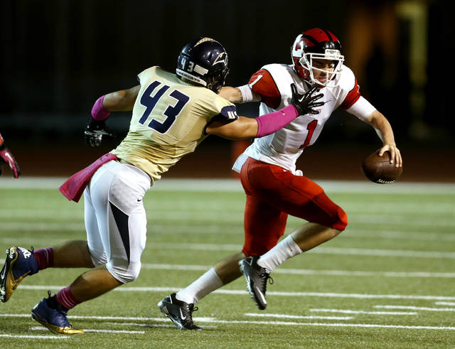 Lawton's Dallas Sealey (1) tries to get past Reece Gilbert as the Southmoore Sabercats play the Lawton High School Wolverines in high school football on Friday, Oct. 11, 2013, in Moore, Okla. Photo by Steve Sisney, The Oklahoman