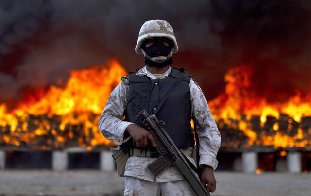 A soldier guards next to packages of marijuana that are being incinerated in Tijuana, Mexico, Wednesday, Oct. 20, 2010. On a conjoined operation with the army, local and state police seized 134 tons of U.S.-bound marijuana Monday, by far the biggest drug bust in the country in recent years. Eleven suspects were detained.(AP Photo/Guillermo Arias)