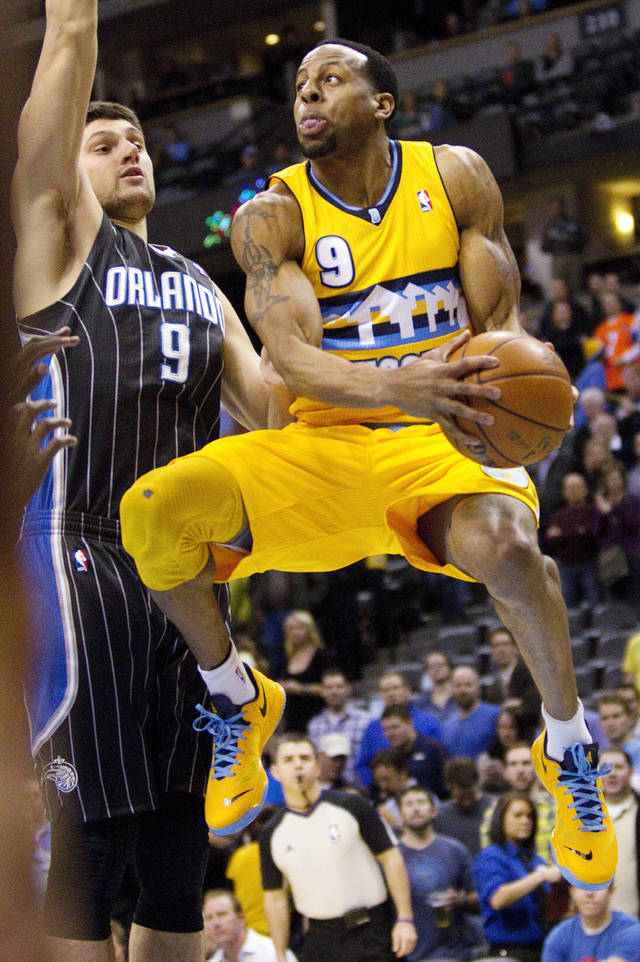 Denver Nuggets' Andre Iguodala (9) drives to the basket past Orlando Magic's Nikola Vucevic (9) during the first quarter of an NBA basketball game, Wednesday, Jan. 9, 2013, in Denver. (AP Photo/Barry Gutierrez)