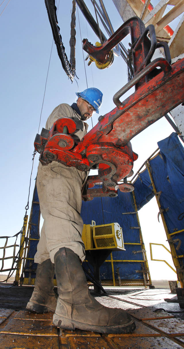 Floorman Paul Tabarez gets the breakout tongs reedy to pull pipe on a SandRidge oil drilling rig near Medford, Thursday, October 18, 2012. This is for Oklahoma Inc. Photo By David McDaniel/The Oklahoman