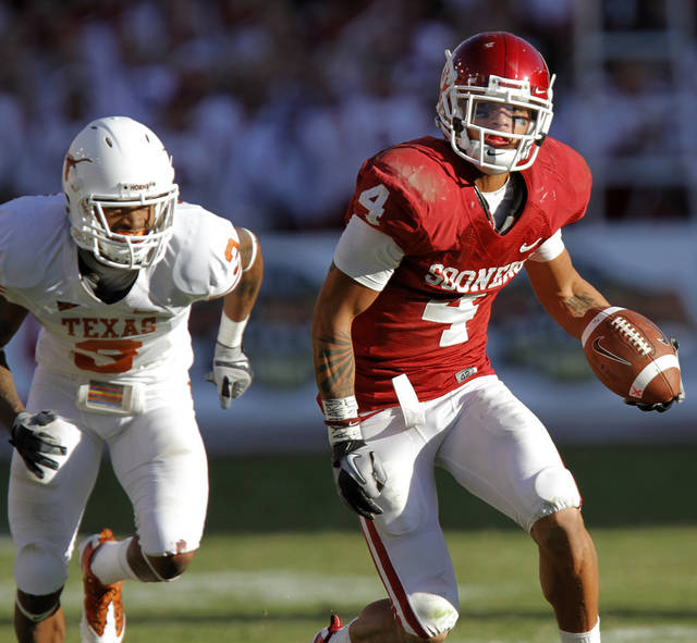 Oklahoma's Kenny Stills (4) takes the ball up field past Texas' Curtis Brown (3) in the second half of the Red River Rivalry college football game between the University of Oklahoma Sooners (OU) and the University of Texas Longhorns (UT) at the Cotton Bowl on Saturday, Oct. 2, 2010, in Dallas, Texas.   Photo by Chris Landsberger, The Oklahoman