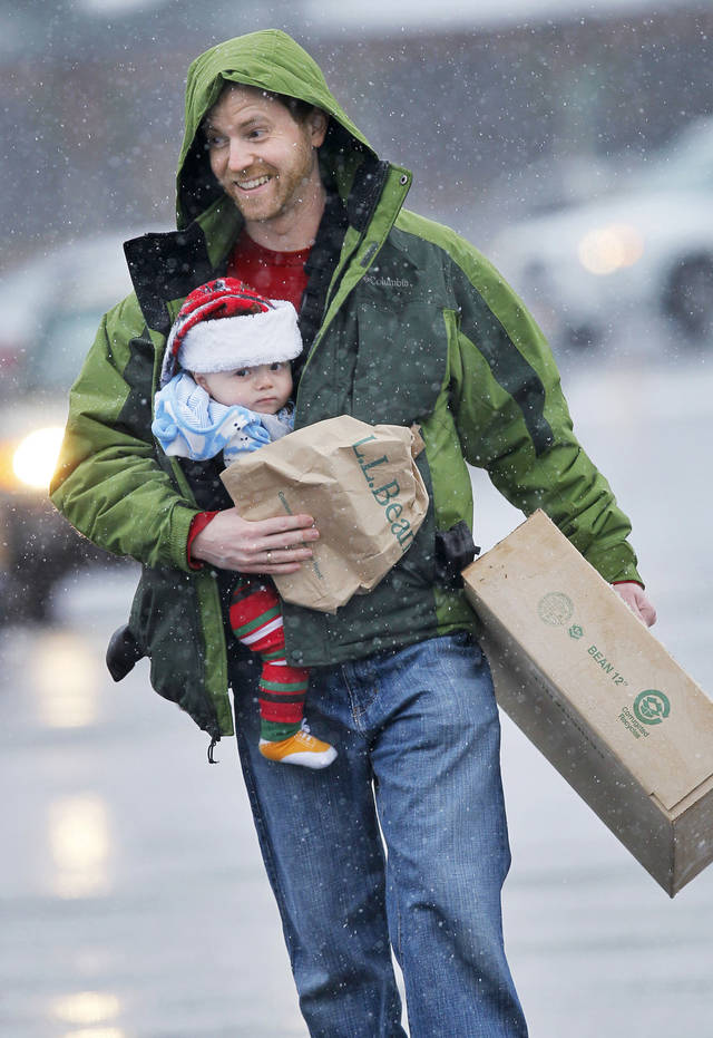 Chris Palmer, of Topsham, Maine, has his arms full carrying his 10-month-old son, Jameson, and some last-minute Christmas gifts he bought at L.L. Bean in Freeport, Maine.  AP Photo