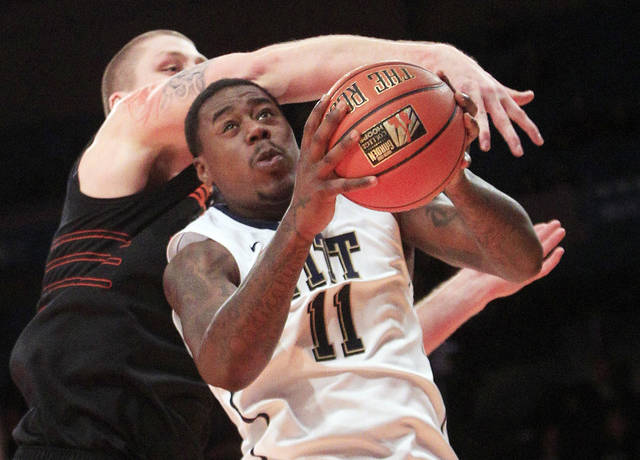 Pittsburgh's Dante Taylor (11) goes to the basket as Oklahoma State's Philip Jurick (44) defends during the second half of an NCAA basketball game at the CARQUEST auto parts classic, Saturday, Dec. 10, 2011, in New York. Pittsburgh won 74-68. (AP Photo/Frank Franklin II). ORG XMIT: MSG128