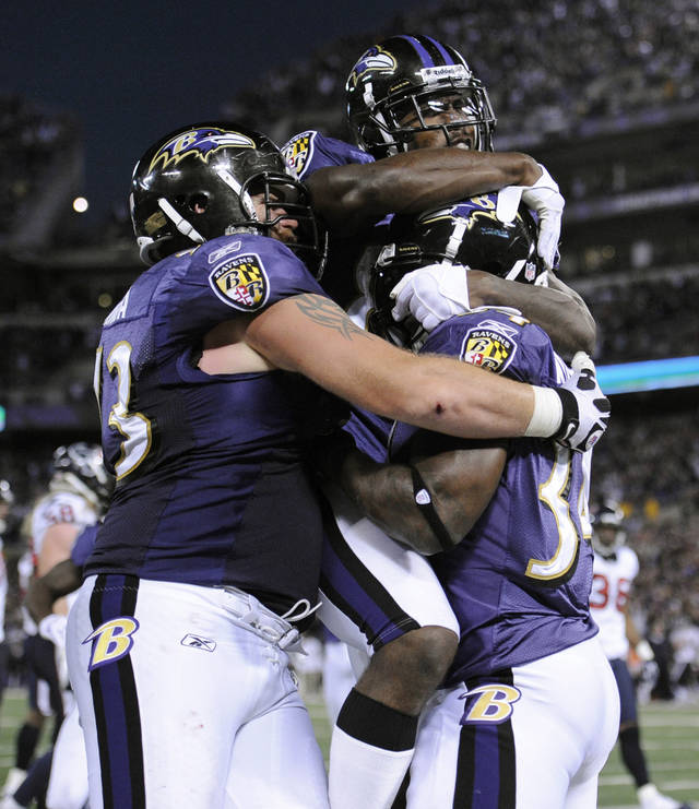 Baltimore Ravens offensive guard Marshal Yanda, left, and wide receiver Anquan Boldin, top, hug running back Ricky Williams after Williams scored a touchdown in the second half of an NFL football game against the Houston Texans in Baltimore, Sunday, Oct. 16, 2011. (AP Photo/Nick Wass)