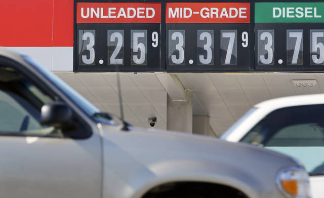 FILE - In this Oct. 30, 2012 file photo, traffic drives past a North Little Rock, Ark., gas station. Gas prices are dropping just in time for holiday travel. By Monday, Dec. 17, 2012, the national average should fall below $3.2775 a gallon, the low for the year set on Jan. 1. But American drivers will still spend a record amount on gas in 2012, with each gallon costing 10 cents more on average than a year ago. They can only hope that government forecasts for lower prices next year come true. (AP Photo/Danny Johnston, File)