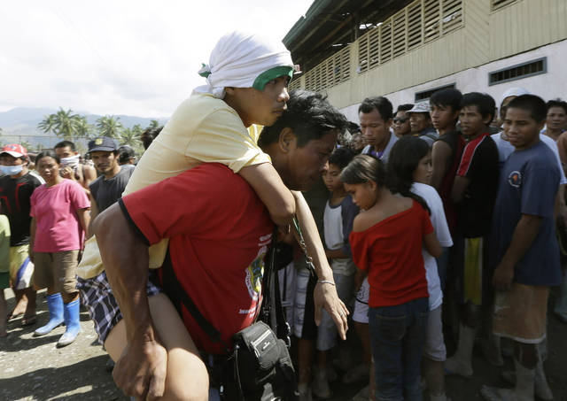 A flash flood victim is carried to a makeshift clinic following Tuesday's devastating typhoon, in New Bataan township, Compostela Valley in the southern Philippines, Thursday, Dec. 6, 2012. The powerful typhoon that washed away emergency shelters, a military camp and possibly entire families in the southern Philippines has killed hundreds of people with nearly 400 missing, authorities said Thursday. (AP Photo/Bullit Marquez)